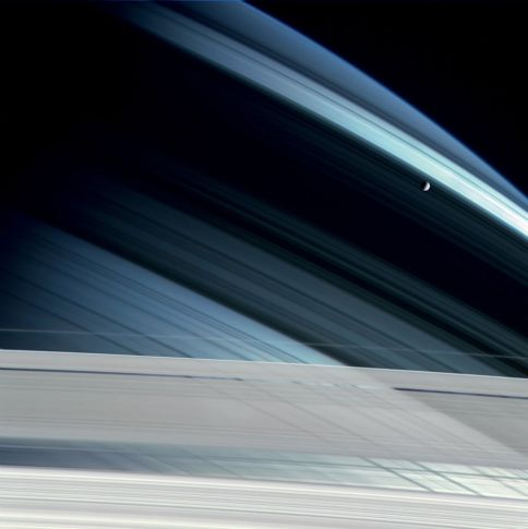 Mimas against shadows cast by Saturn's rings on its northern hemisphere