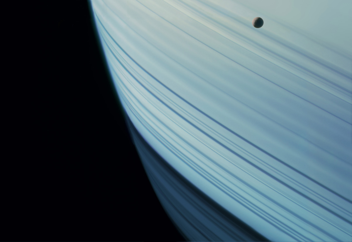 Saturn's tiny moon Mimas in transit across rippling ring shadows on the planet's northern hemisphere during that hemisphere's winter