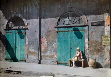 A woman sits outside the doorway of the Absinthe House in New Orleans
